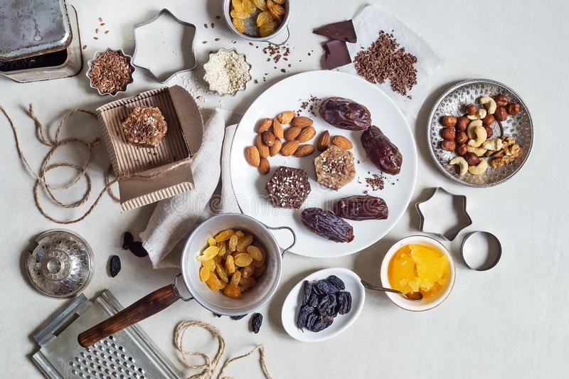 Natural useful sweets from dates, nuts, honey and raisins on a white plate. These ingredients are next on the table stock photos