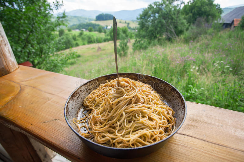 Natural view and pan with Italian pasta with tomato and fork. Spaghetti food on terrace of rural home. As a symbol of the village life royalty free stock images