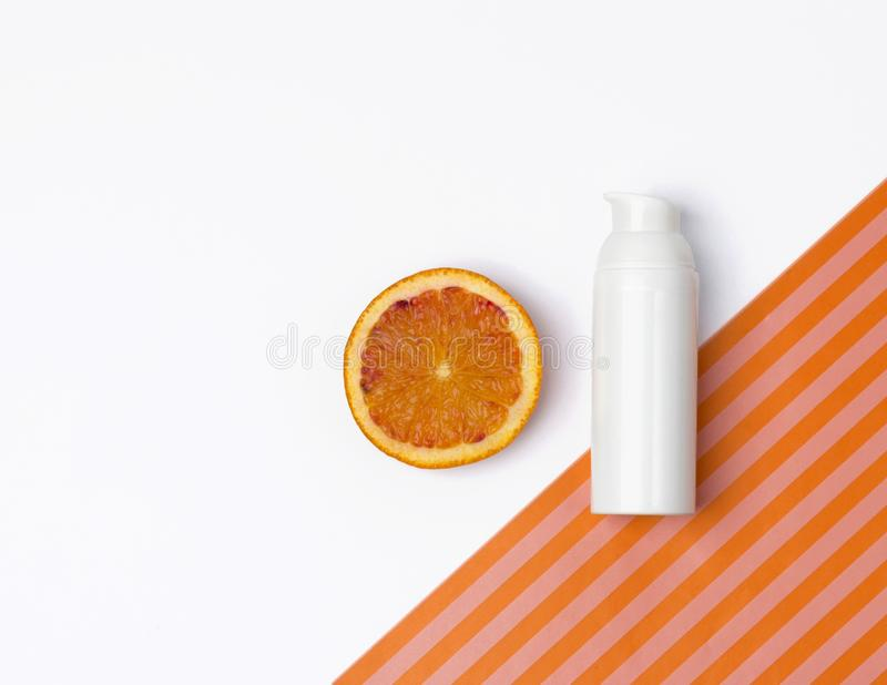 Natural vitamin c skincare product with orange fruit slices on white  background. Moisturizing cream or body lotion with. Cosmetic beauty product branding mock royalty free stock images