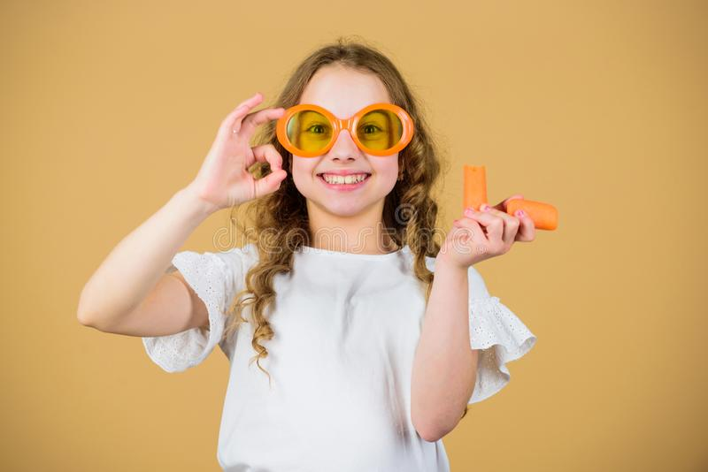 Natural vitamin source. Girl eat carrot vegetable and drink carrot juice. Vitamin nutrition. Fashion kid sunglasses royalty free stock images