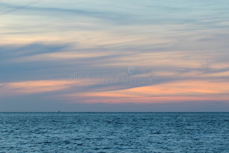 Natural washed pastel cloudscape. Sea and wispy cloud sky at dawn. Soft background image. Painterly watercolor backdrop unaltered landscape sunrise. Simple royalty free stock photo