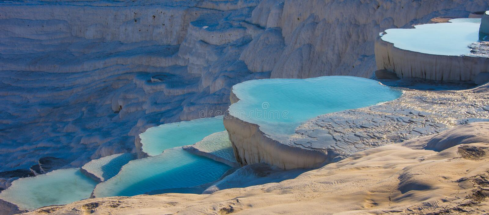 The natural white stone swimming pools fill with the thermal water. In the Pamukkale in Turkey royalty free stock photo