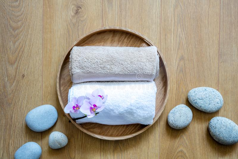 Natural white towels and ayurveda pebbles on wooden background stock photography