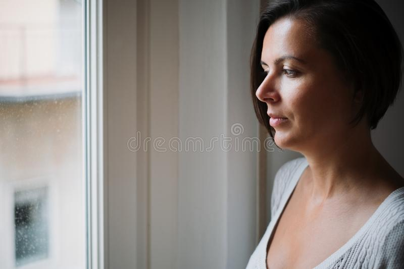 Natural woman looking out the window stock images
