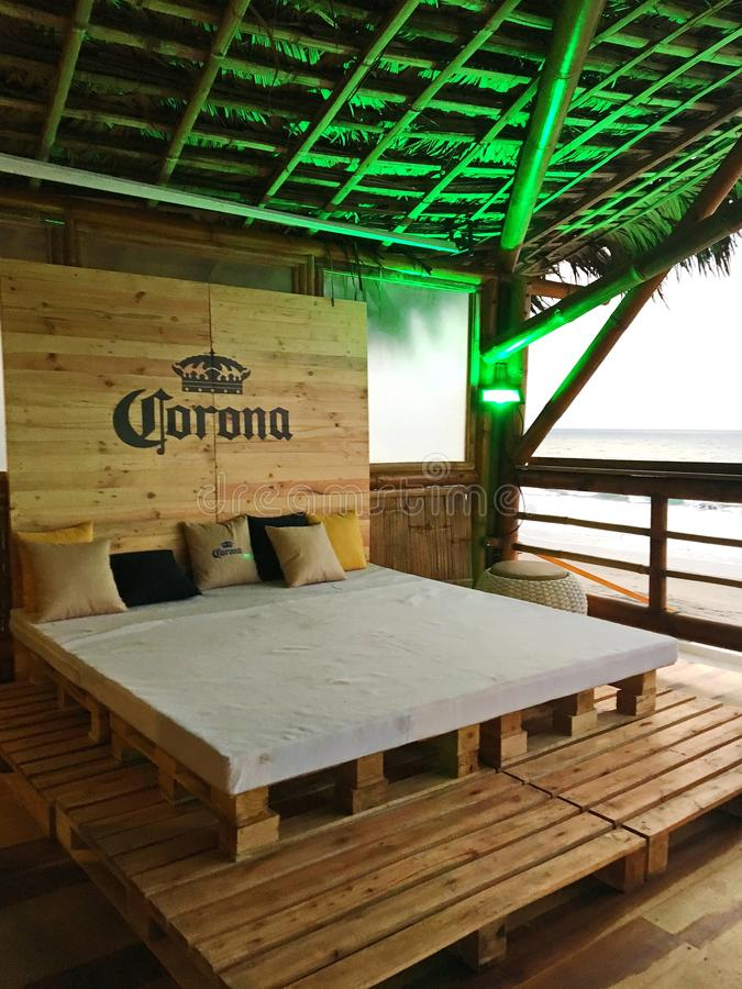 Corona Lounge Bed Overlooking the Ocean. Natural wood headboard with Corona logo and bed on wood slats is a focal point on second story of Ecuablue, a bar built royalty free stock image