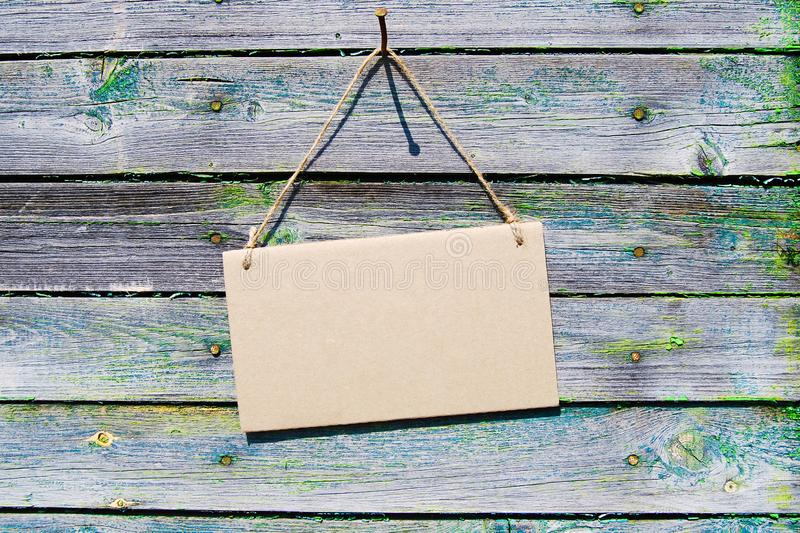Natural wooden backdrop, brown empty cardboard notice hanging on rope. Natural wood backdrop, brown empty cardboard notice hanging on rope. Mockup, horizontal royalty free stock photography