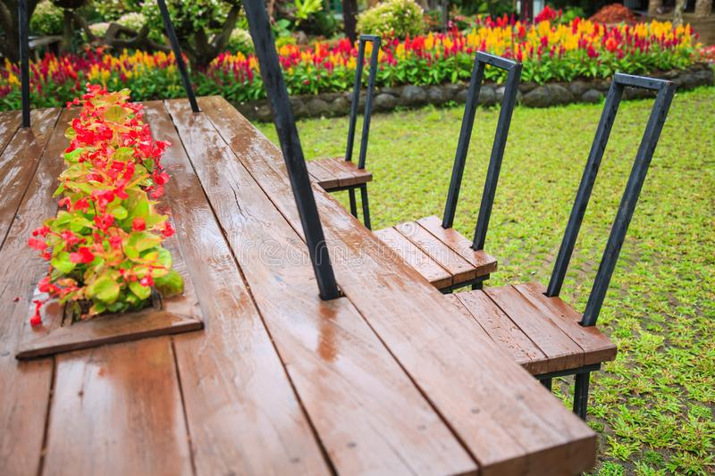 Natural wooden chairs and table in park in middle of variety of decorative ornamental flower gardens. Summer Outdoor Family Activi royalty free stock images