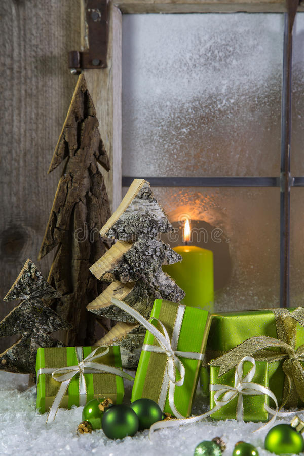 Natural wooden christmas decoration with candles and green presents. stock photos