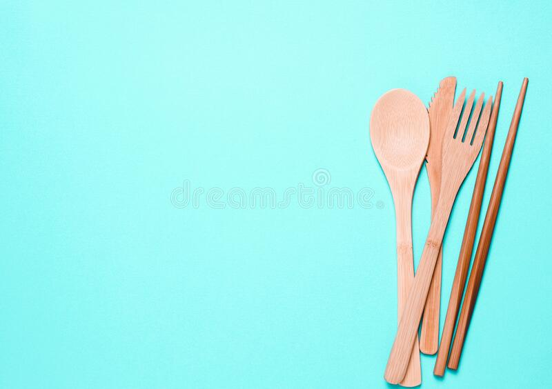 Natural, wooden fork, spoon, cutlery on a blue background royalty free stock image