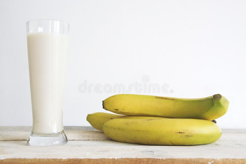 Natural yellow bananas on a white wooden table and a fruit shake smoothie against a white background. Empty copy space stock photos