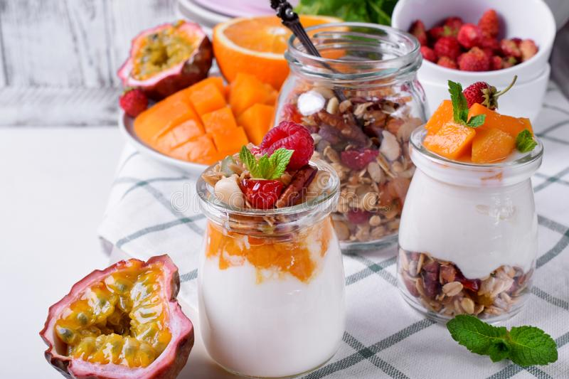 Natural yogurt, granola and mashed passion fruit and mango layered in a glass jar royalty free stock photography