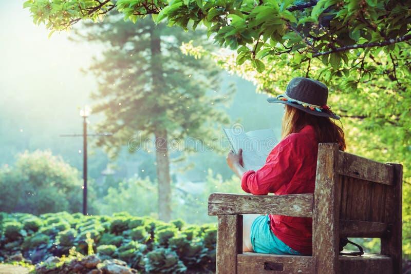 Naturaleza asi?tica del viaje de la mujer El viaje se relaja Lea el libro en el banco en el parque en verano fotos de archivo