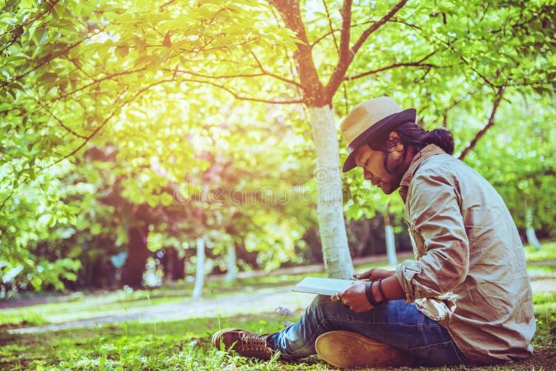 Naturaleza asi?tica del viaje del hombre El viaje se relaja libro de lectura del sueño en el césped en el parque En verano fotografía de archivo