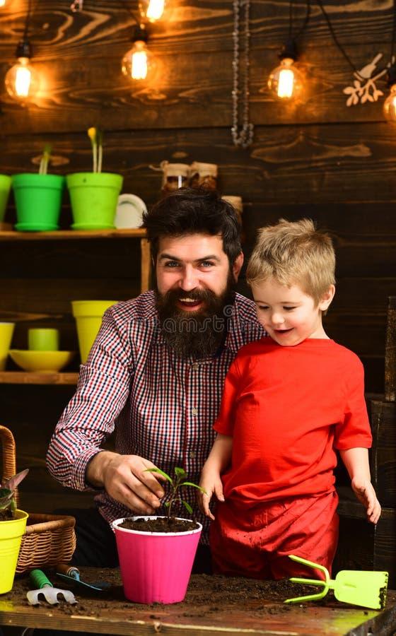 Naturaleza barbuda del amor del ni?o del hombre y del ni?o peque?o Padre e hijo D?a de padres jardineros felices con las flores d fotos de archivo libres de regalías