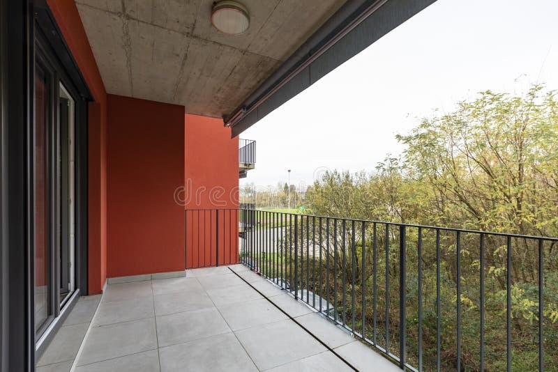 Naturaleza de desatención de la terraza del apartamento con las paredes exteriores rojas fotos de archivo