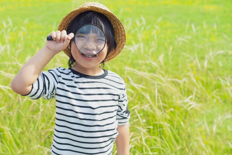 Naturaleza de exploración del muchacho joven en el prado con una lupa que mira las flores Niños curiosos en el bosque imagen de archivo libre de regalías
