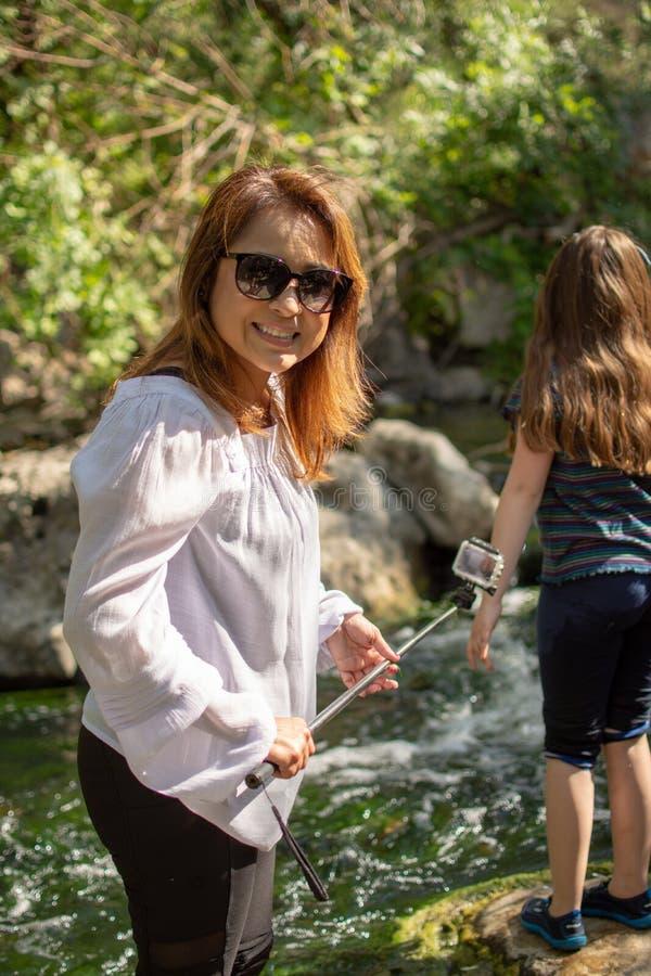 Naturaleza de exploración de la mujer y de la hija junto en una corriente o un río fotografía de archivo