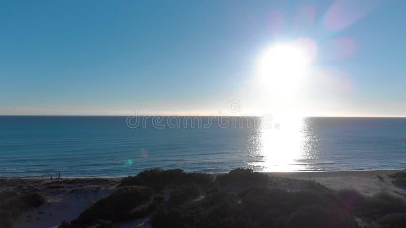 Naturaleza hermosa de Nueva Zelanda, mar, campos verdes, prados, colinas y gente en la orilla Arte Puesta del sol brillante sobre foto de archivo