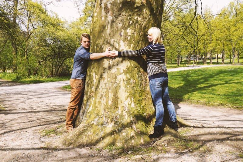 Naturaleza que ama los pares jovenes que abrazan el tronco de árbol fotografía de archivo