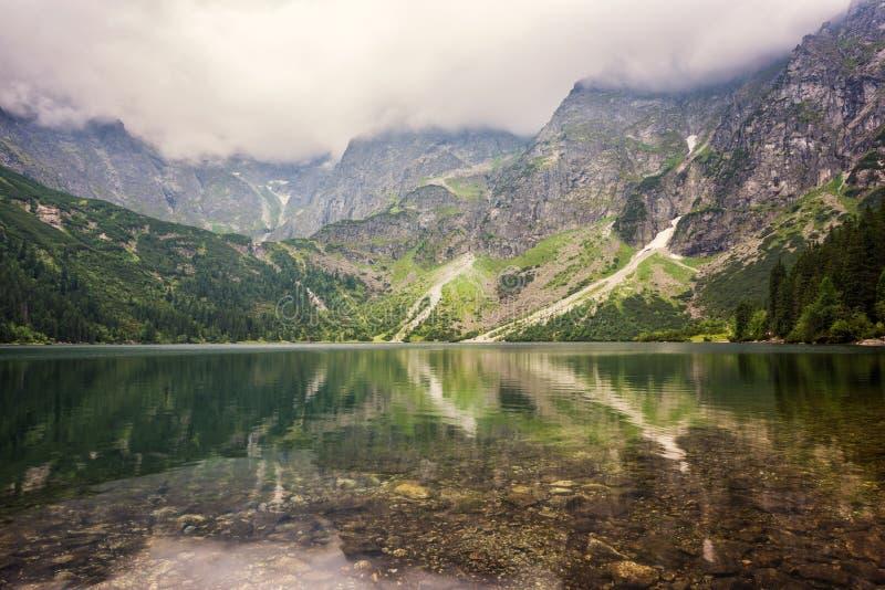 Naturaleza que sorprende, lago alpino en las montañas, paisaje del verano con el cielo nublado y reflexión en agua cristalina imagen de archivo