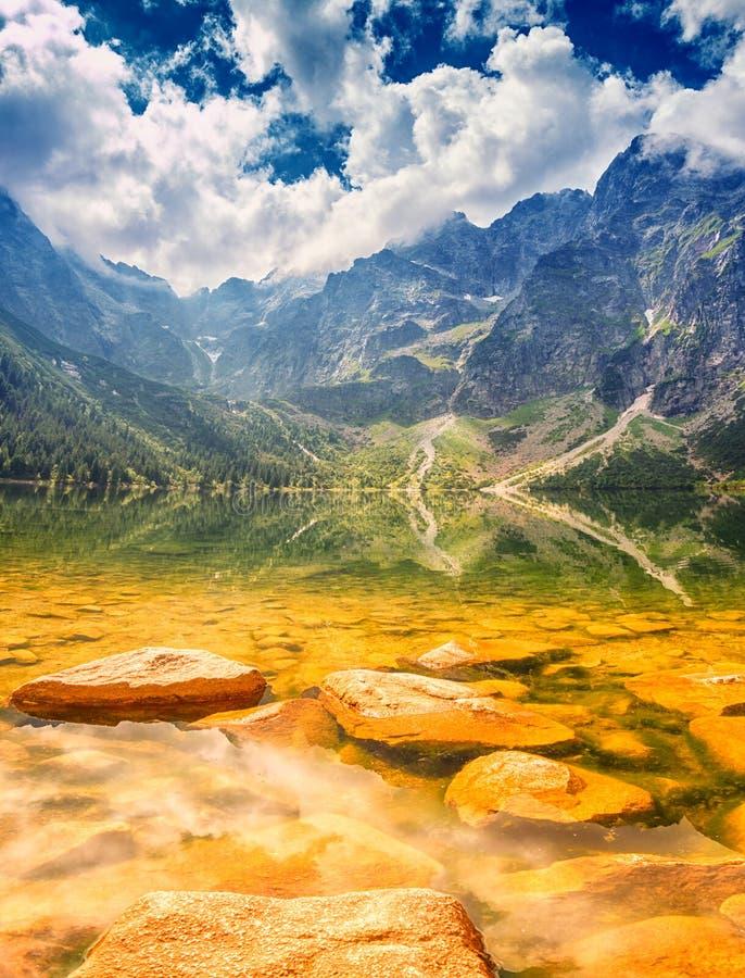Naturaleza que sorprende, lago alpino en las montañas, paisaje escénico del verano con el cielo nublado azul y reflexión en el ag imagen de archivo