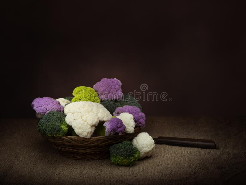 Naturally colourful vegetables in basket, chiaroscuro style dark still life. Assorted raw cauliflower, with broccoli royalty free stock image