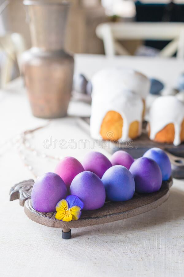 Naturally dyed Easter hen`s eggs with a vioet flower on linen background. Naturally dyed hen`s eggs with a violet flower on linen background, Easter spring stock photo