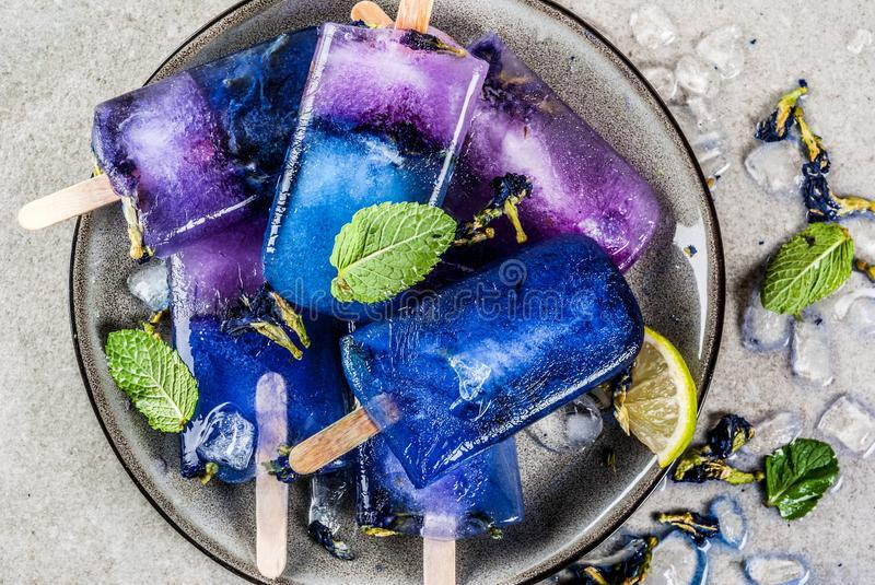 Butterfly pea flower popsicles. Naturally organic summer sweets, homemade blue and violet ice cream popsicles with butterfly pea flower tea, grey concrete royalty free stock photos