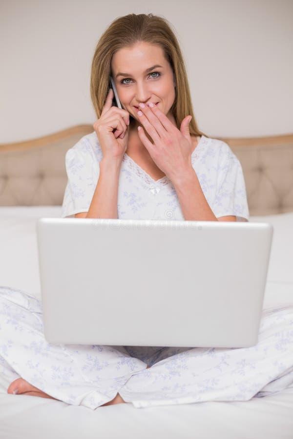 Naturalna zdziwiona kobieta używa laptop i dzwonić obrazy stock