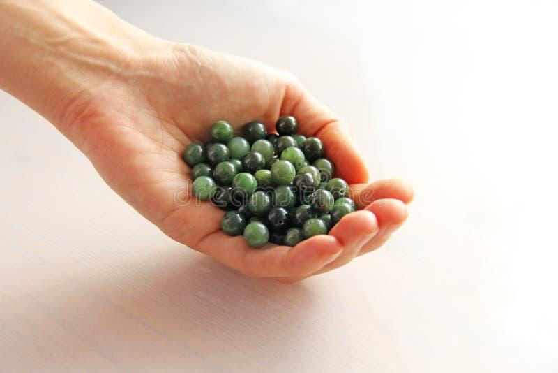 Naturalna zielona chabeta nefrytu kopalina dryluje koraliki Zielony chabeta kamień kłama w rękach Ręki trzyma kamiennymi na biały obraz royalty free