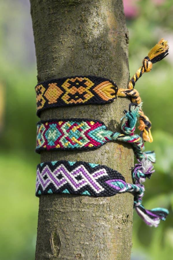 Naturalne bransoletki przyjaźń na gałąź, kolorowe wyplatać przyjaźni bransoletki, zielony tło, tęcza barwią zdjęcie royalty free