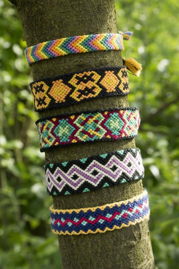 Naturalne bransoletki przyjaźń na gałąź, kolorowe wyplatać przyjaźni bransoletki, zielony tło, tęcza barwią obrazy stock