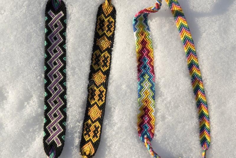 Naturalne bransoletki przyjaźń z rzędu, kolorowe wyplatać przyjaźni bransoletki, śnieżny tło, tęcza barwią, w kratkę wzór obrazy stock