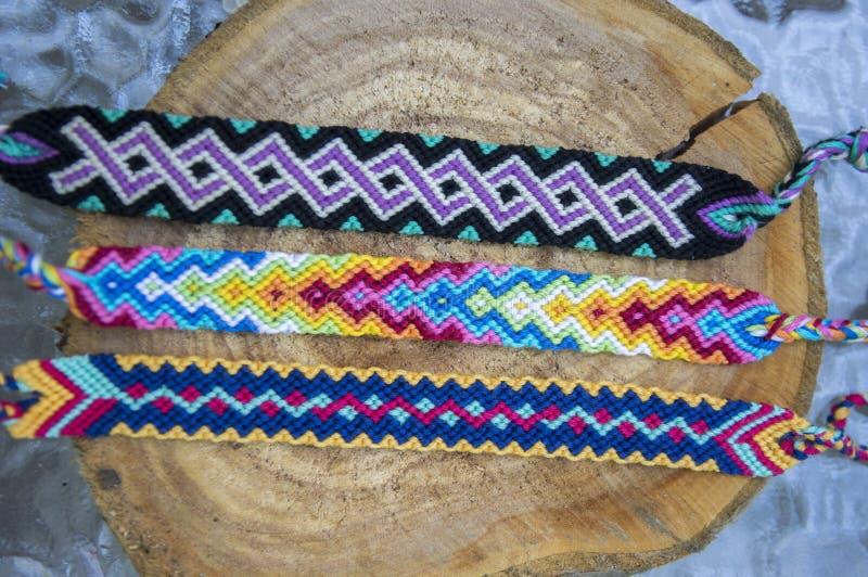 Naturalne bransoletki przyjaźń z rzędu, kolorowe wyplatać przyjaźni bransoletki, tło, tęcza barwią, w kratkę wzór fotografia stock