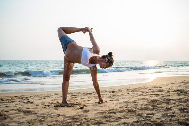 Naturalnego przyglądającego kobieta w ciąży ćwiczy joga przy seashore a obraz stock