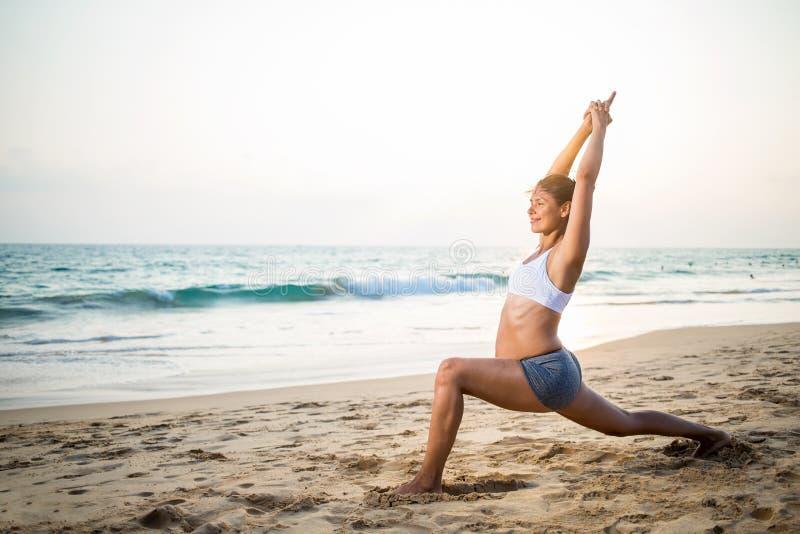 Naturalnego przyglądającego kobieta w ciąży ćwiczy joga przy seashore a obrazy stock
