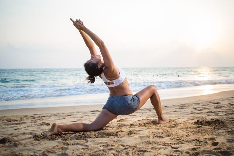 Naturalnego przyglądającego kobieta w ciąży ćwiczy joga przy seashore a zdjęcie royalty free