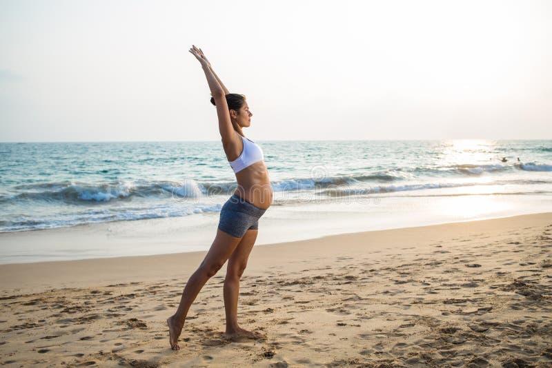 Naturalnego przyglądającego kobieta w ciąży ćwiczy joga przy seashore a fotografia stock