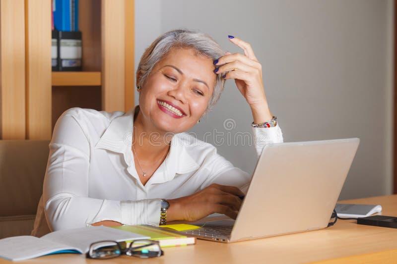 Naturalnego styl ?ycia biurowy portret atrakcyjna i szcz??liwa pomy?lna dojrza?a Azjatycka kobieta pracuje przy laptopu biurka on zdjęcie stock