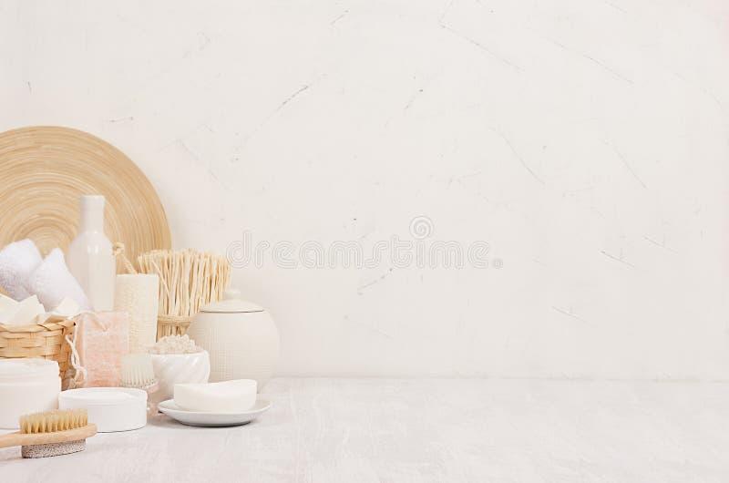 Naturalnego zdroju kosmetyków biali produkty i beżowy bambusowy nieociosany wystrój na białym drewnianym tle, wnętrze, granica zdjęcia stock