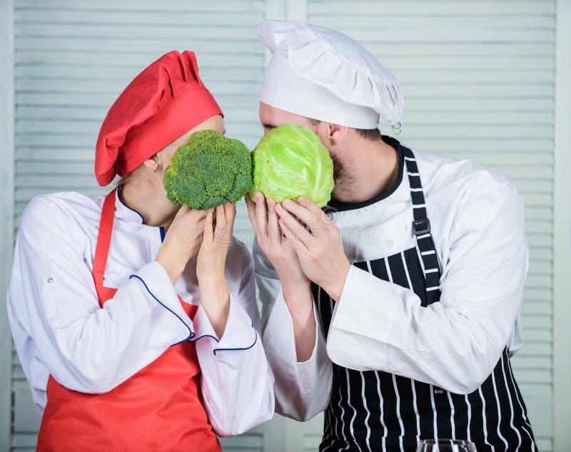 Naturalni brokuły i kapusta Rodzinny kucharstwo w kuchni jarosz kucharz mężczyzny i kobiety szef kuchni trzyma brokuły i kapusty fotografia royalty free