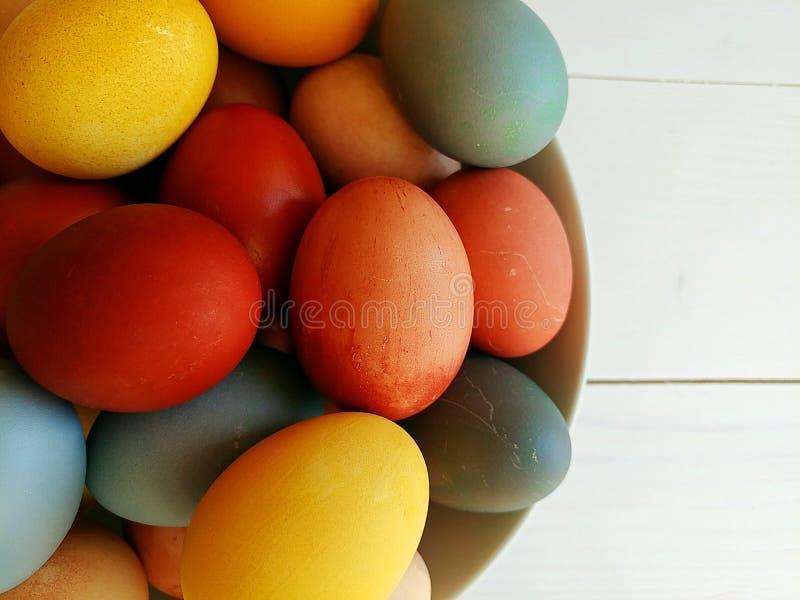 Naturalni farbujący jajka w talerzu na białym drewnianym tle 2 forsują pisklęca pojęcia Easter jajek kwiatów trawa malujących umi fotografia royalty free