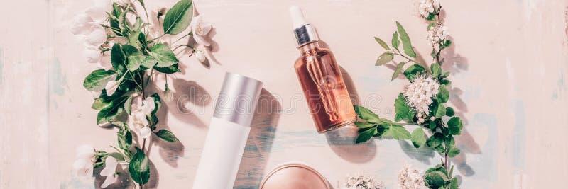 Naturalni organicznie kosmetyki: serum, śmietanka, maska na drewnianym tle z kwiatami Zdroju pojęcie obrazy royalty free