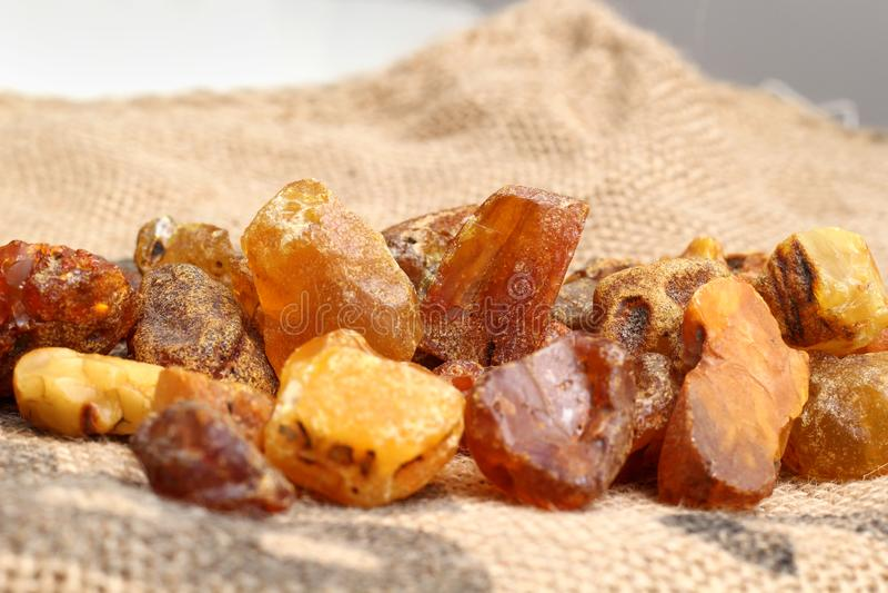 Naturalni surowi bursztynów kamienie na jutowym torby tle Wieloskładnikowy złocisty gemstone w różnorodnych kształtach i colour B obraz stock