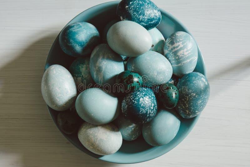 Naturalnie farbujący Wielkanocni błękitni jajka, rozpraszający na błękita talerzu na whi, zdjęcia stock