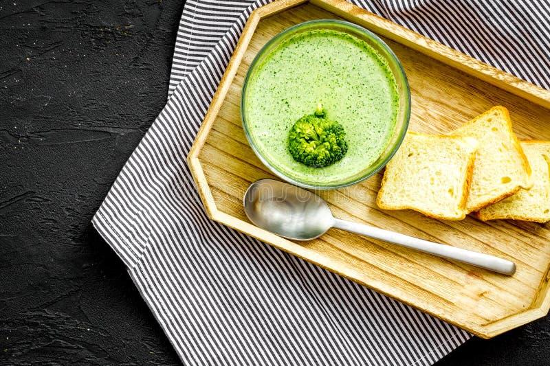 Naturalny, żywność organiczna Zielony jarzynowy puree w pucharze przygotowywającym jeść słuzyć z rusks na czarnej stołowej odgórn fotografia stock