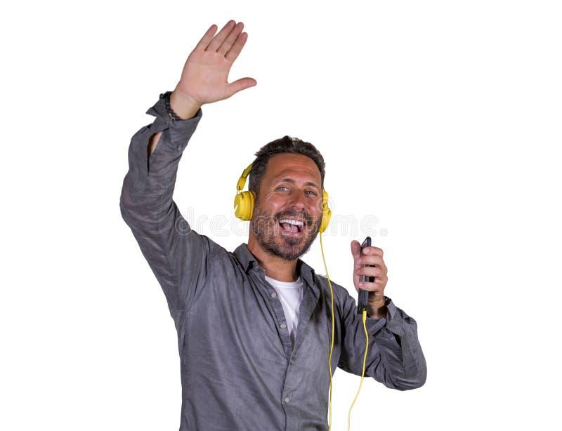 Naturalny portret 40s szczęśliwy i z podnieceniem atrakcyjny mężczyzna słucha online muzykę z hełmofonami i telefon komórkowy śpi obraz stock