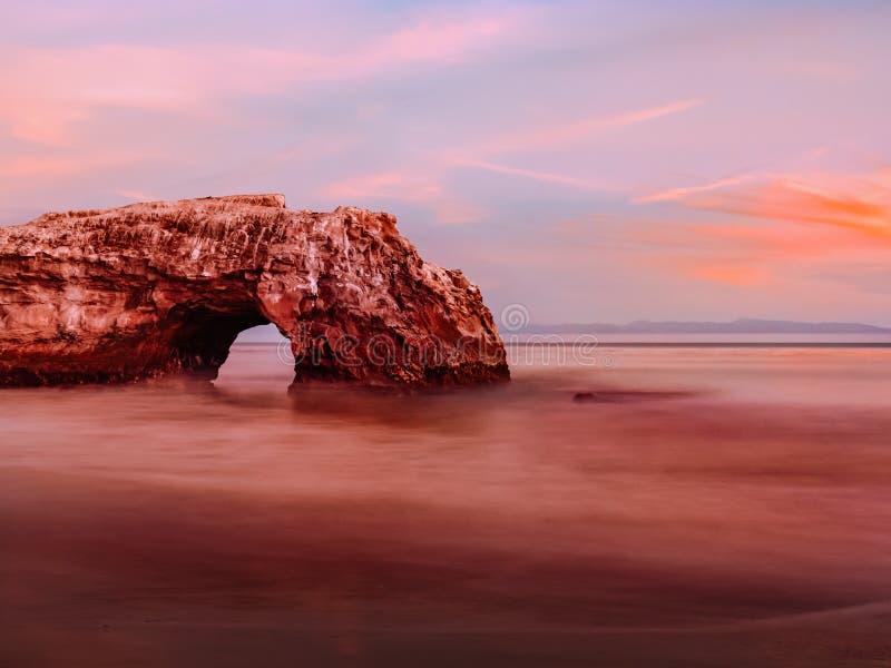 Naturalny skała łuk na ocean spokojny plaży w długim ujawnieniu fotografia stock