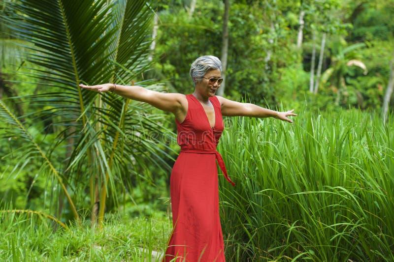 Naturalny styl ?ycia portret pi?kna, szcz??liwa w ?rednim wieku Azjatycka kobieta z popielatym w?osy w eleganckim czerwieni sukni obraz stock