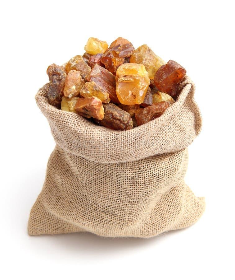Naturalny surowy bursztynu kamień w jutowej torbie odizolowywającej na białym tle Wieloskładnikowy złocisty gemstone w różnorodny zdjęcie stock